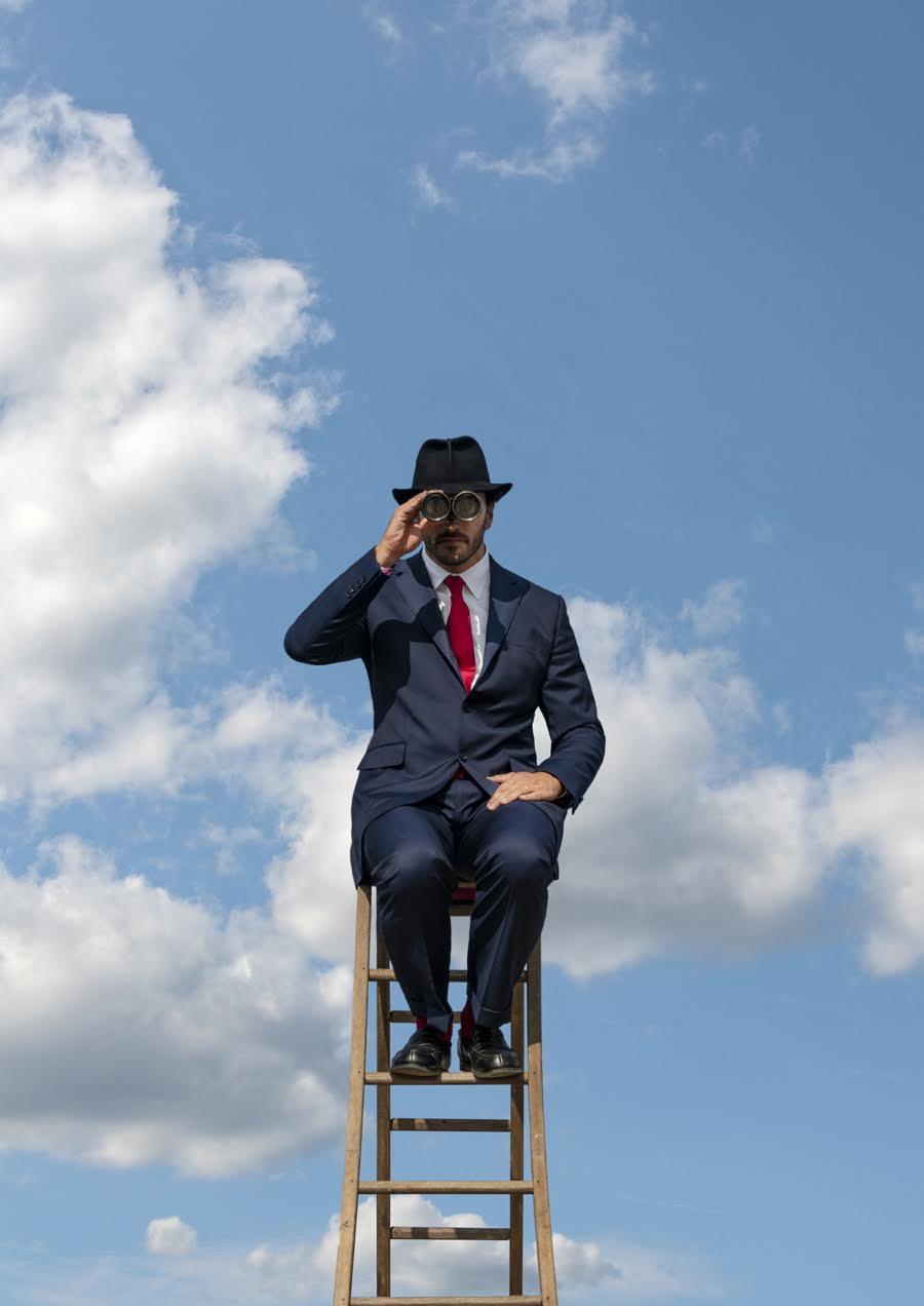 Un homme avec des jumelles sur une échelle