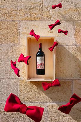 Une bouteille de vin Bélair Monange avec des noeuds rouge