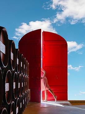 Une femme ouvre une porte rouge Bélair Monange